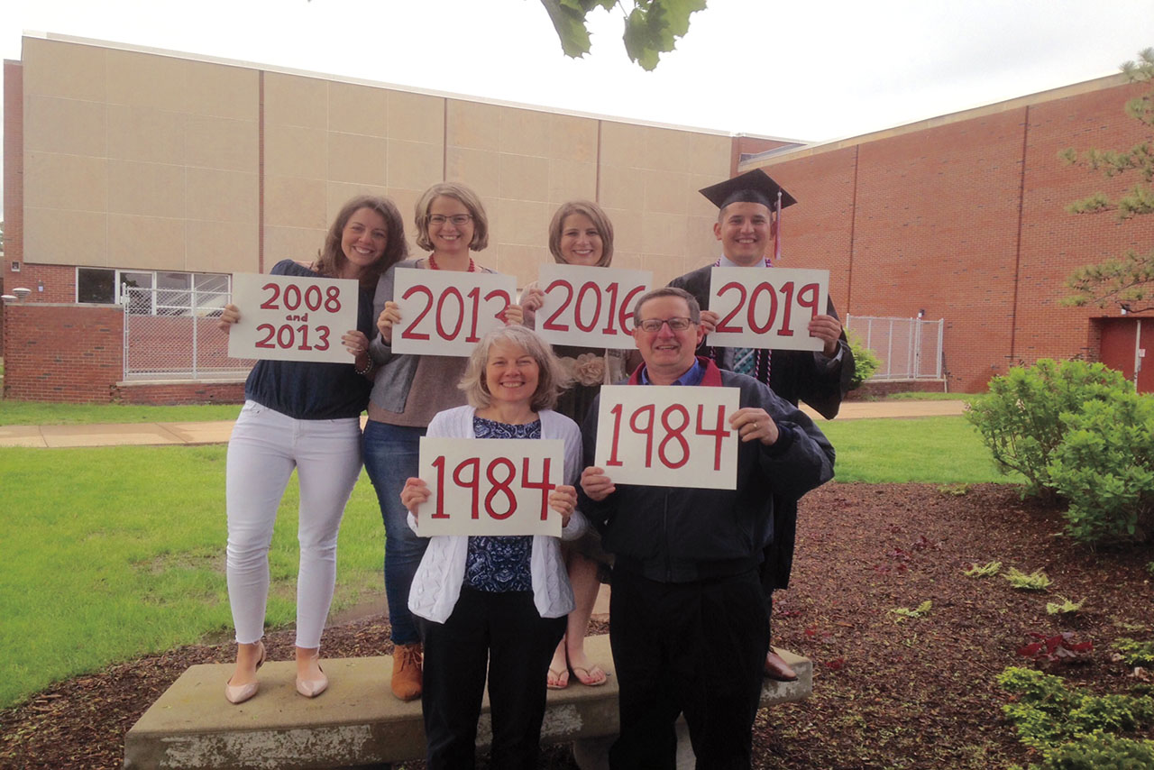 Family of six holding up signs of the years they graduated.