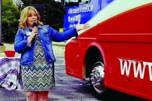 Woman with microphone standing in front of bus
