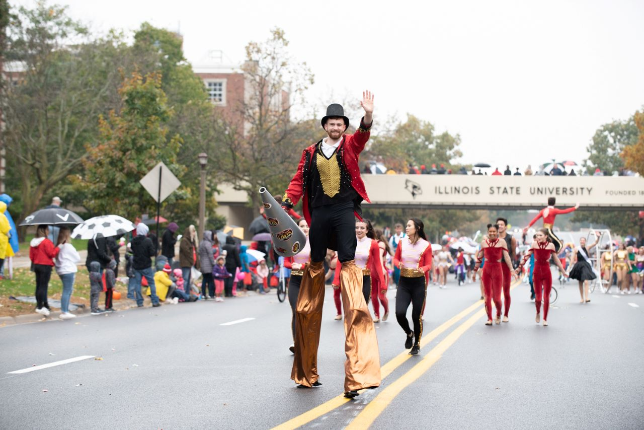 Ringmaster on stilts waving in 2019 ISU Homecoming Parade with performers in the background.