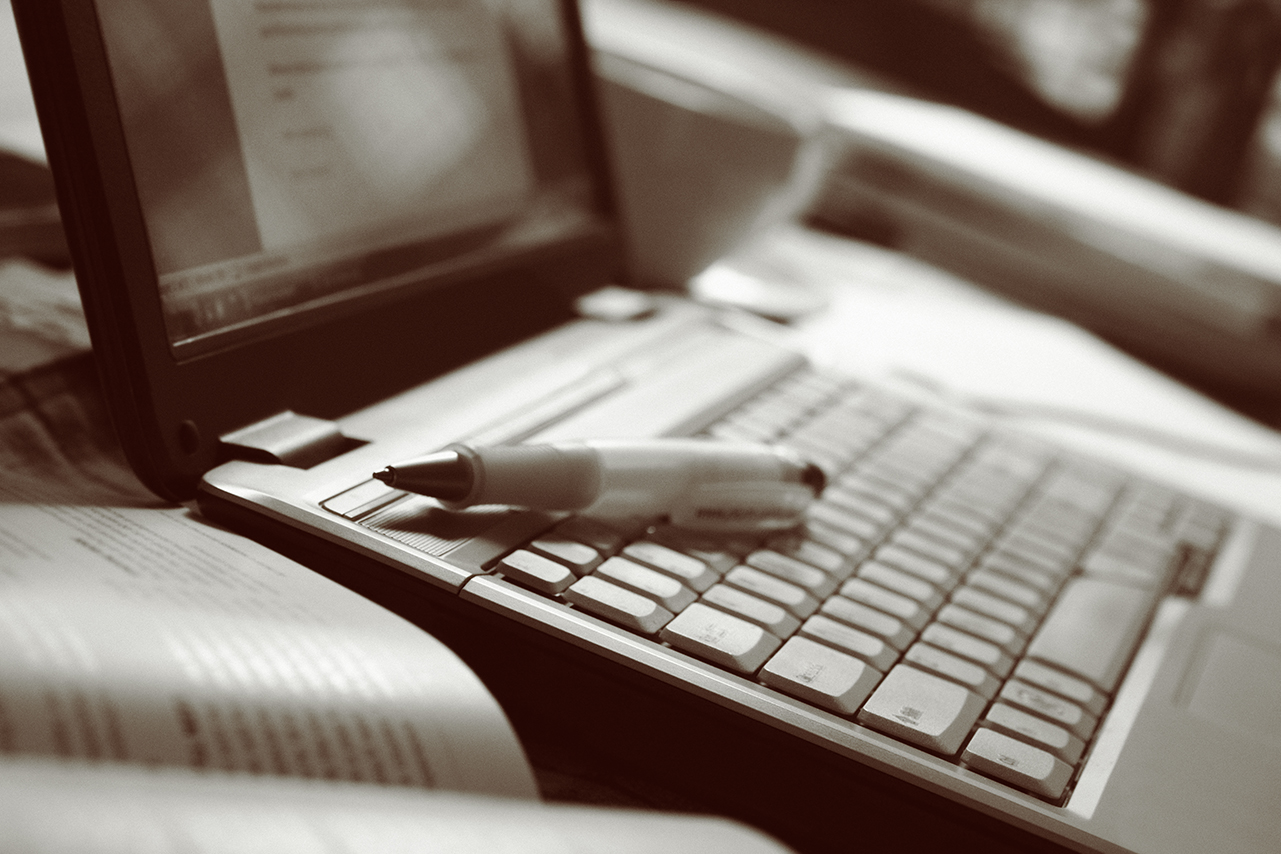 Open laptop with pen, open book and coffee cup on a table. Added grain, sepia toned image.