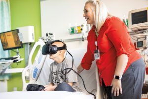 A sick child in a hospital using virtual reality goggles with the founder of the PedsAcademy at the hospital.