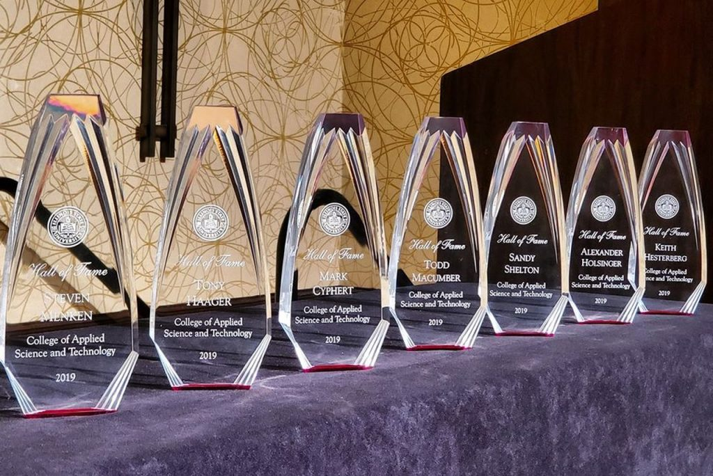 Trophies in a row on a table with a purple tablecloth