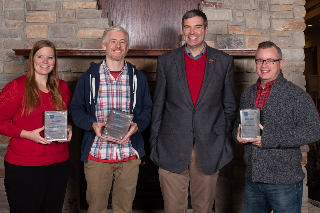 University Marketing and Communications staff display the gold awards they won in the Pride of CASE V competition: senior university photographer Lyndsie Schlink, graphic designer Evan Walles, Executive Director Brian Beam, and graphic designer Sean Thornton.