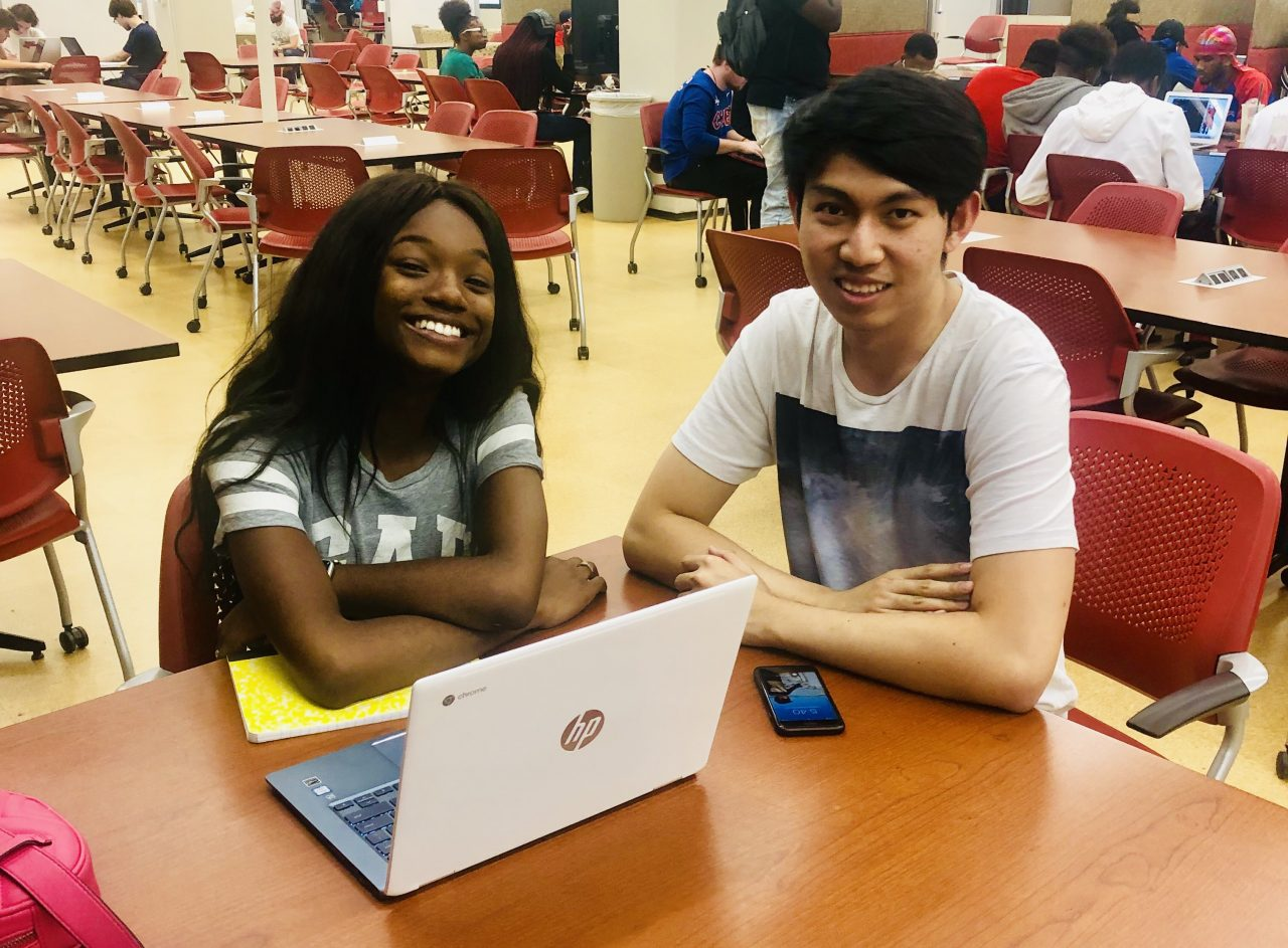 Two college students sitting at a table