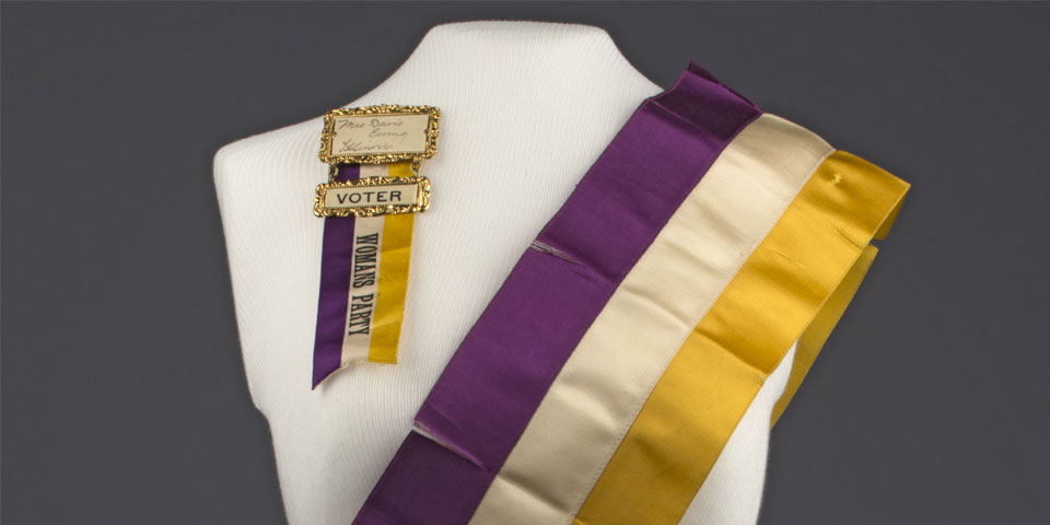 """White dress form wearing a purple, white, and yellow National Woman's Party sash and ribbon reading """"Mrs Davis Ewing Illinois Voter Woman's Party."""""""