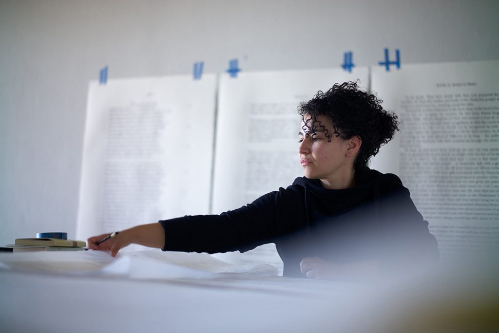 Artist Bethany Collins working in her studio. In the background, pages from books have been enlarged and are hanging on the wall.