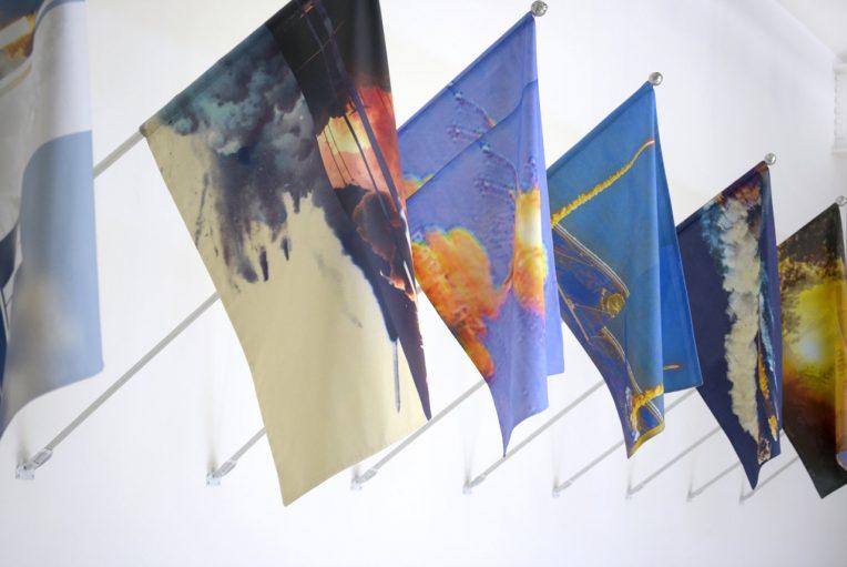 Kambui Olujimi, T-Minus Ø, 2017. Installation of 13 mounted flags. Digital print on cotton with aluminum pole, artist-made finial, zinc pole mount. Courtesy of the artist.