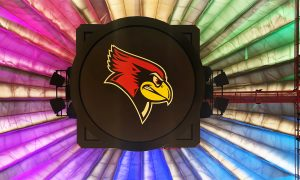 Image of an ISU Redbird against a rainbow background