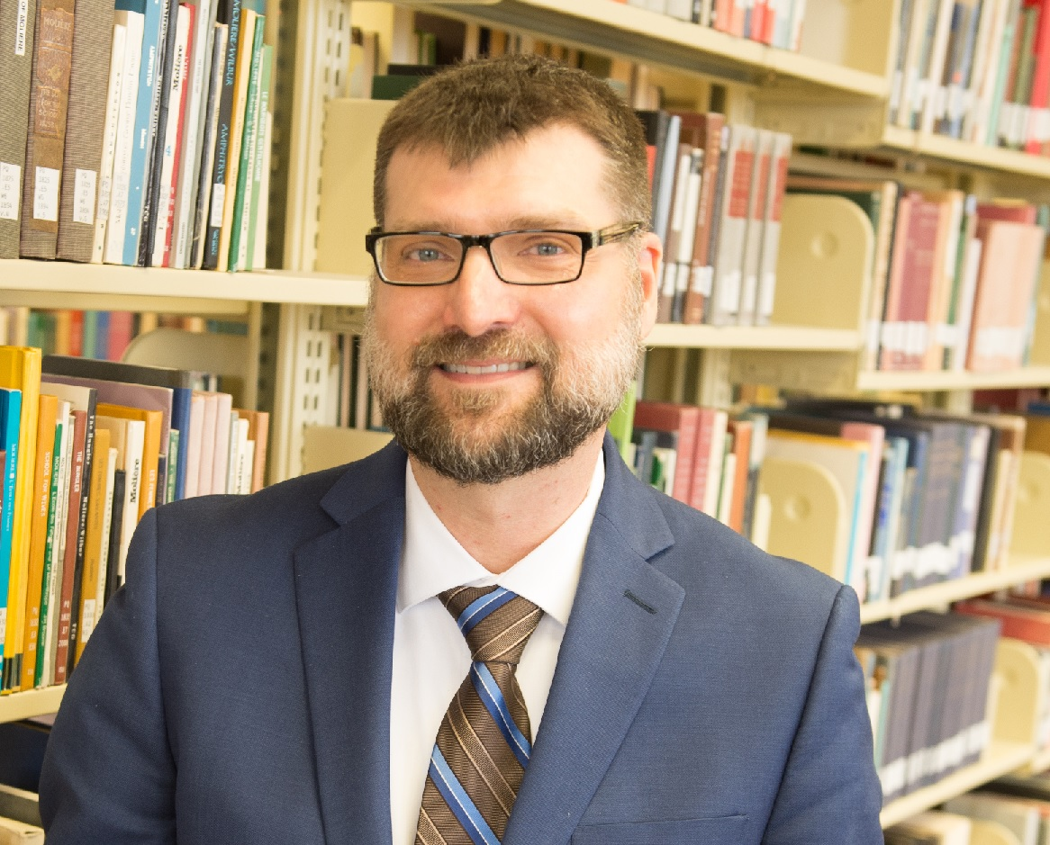 headshot of Dallas Long, in front of shelves of books