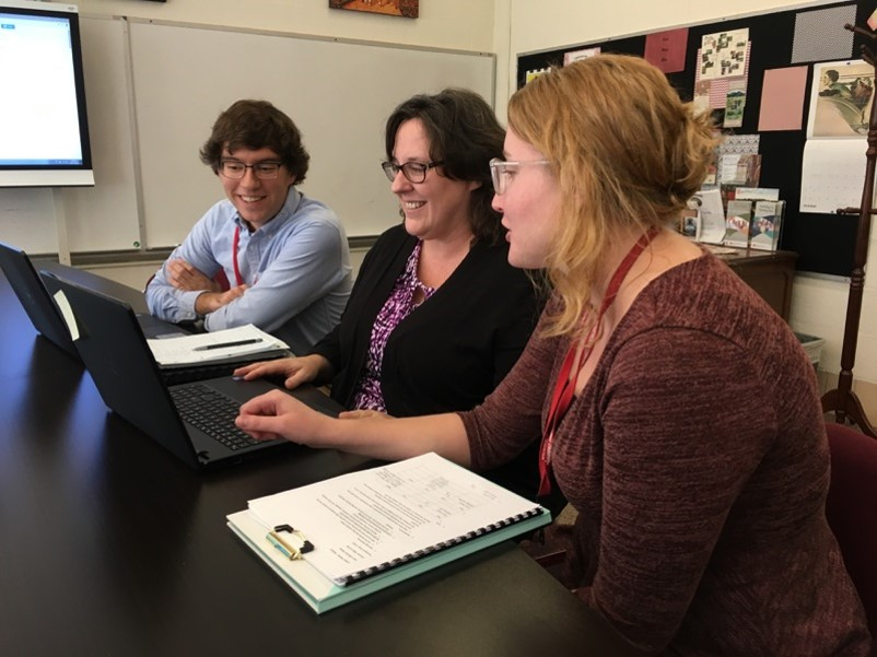 Three people smiling and looking at a laptop