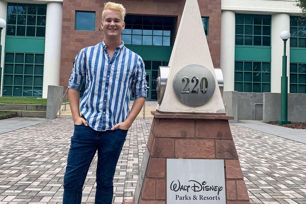 Man standing next to monument for Walt Disney