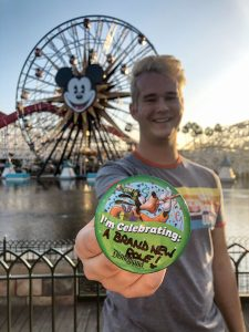 Man standing in front of Mikey Mouse ferris wheel holding a button stating I'm celebrating: A brand new role!