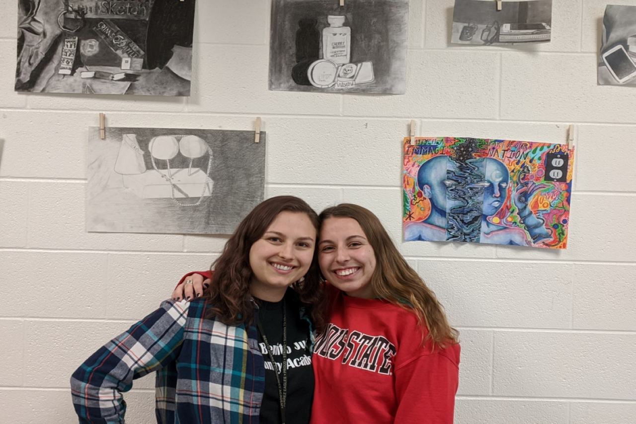 Two teachers pose in front of student art projects