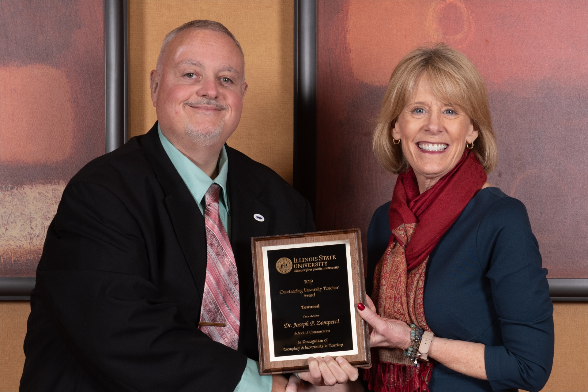 Provost Dr. Jan Murphy presents an Outstanding University Teaching Award to Dr. Joseph Zompetti, School of Communication, who was one of three faculty members so honored at the recent Teaching & Learning Symposium.