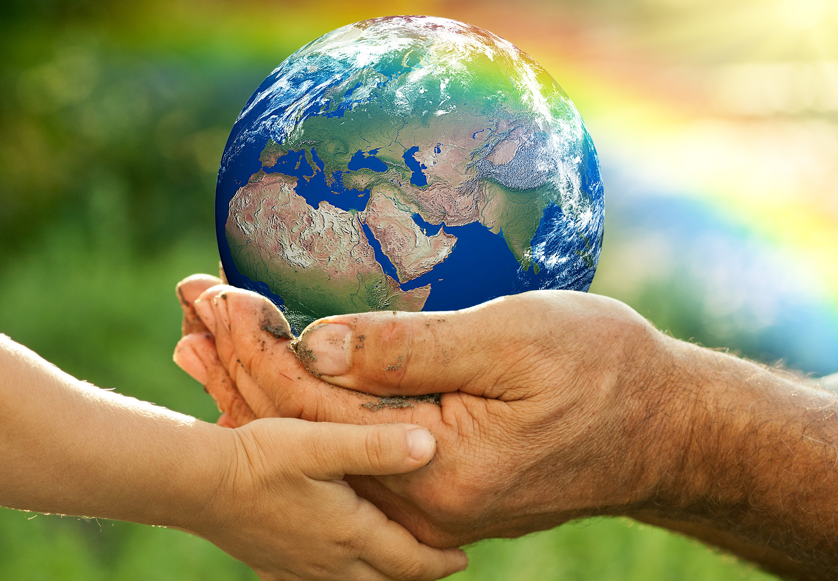 Globe held in hands of older person and child