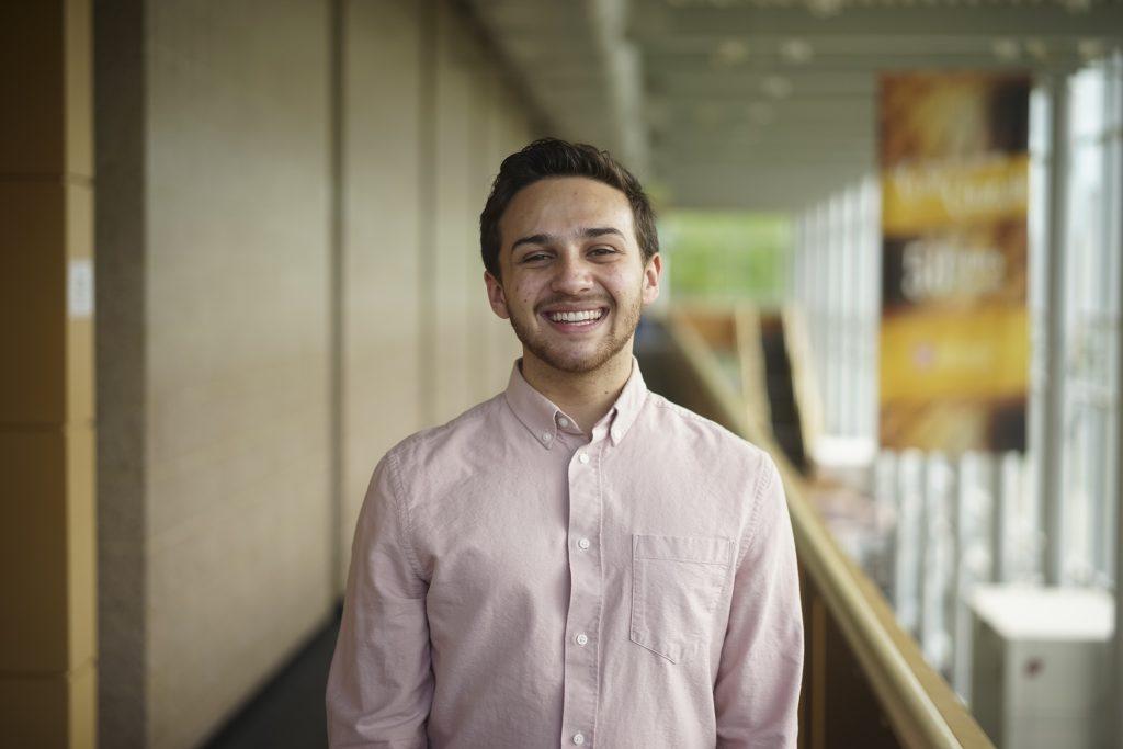 Man standing in hallway, smiling