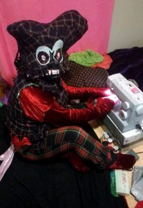 Alumnus Josh Roach dressed as one of his characters, sitting at a sewing machine
