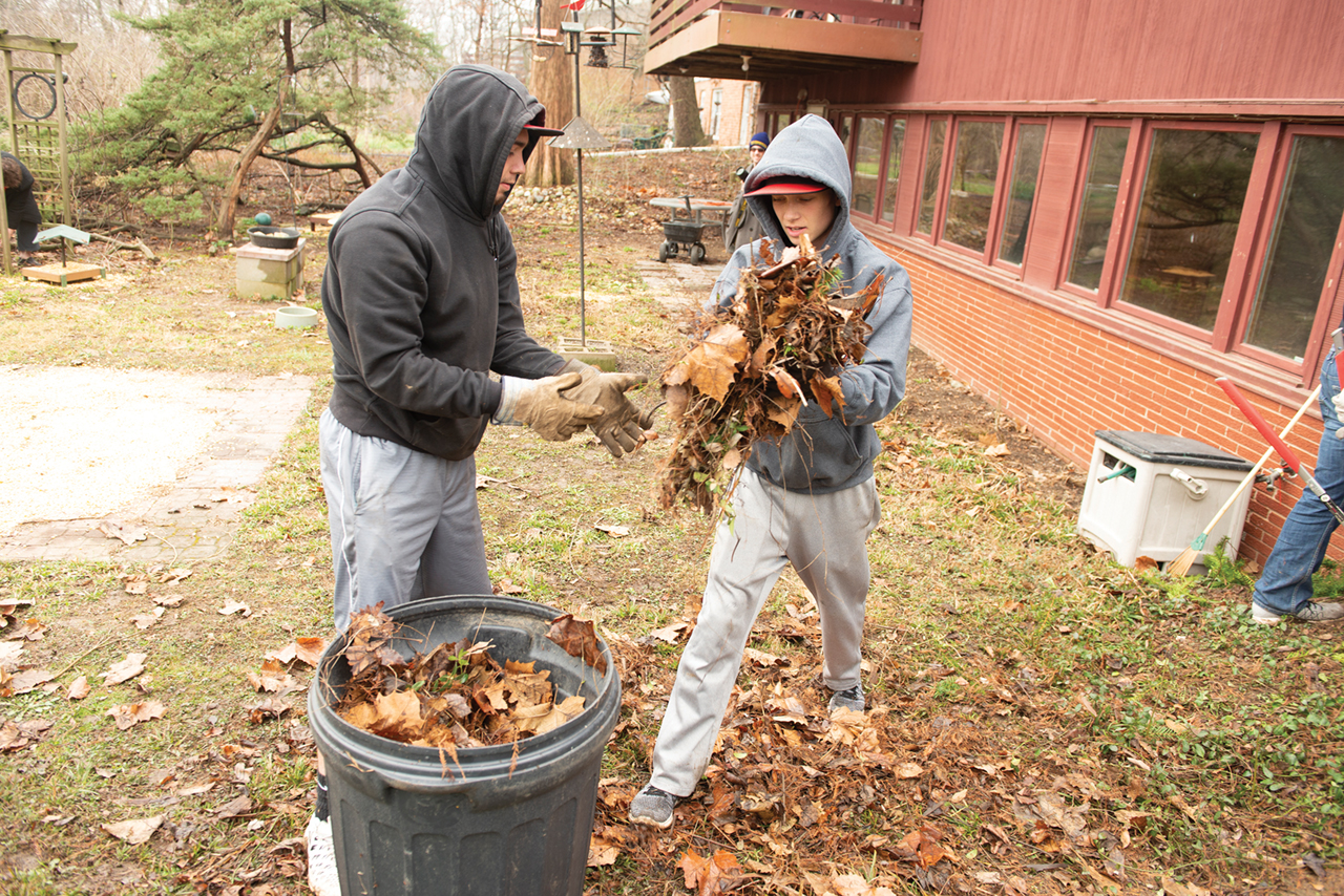 Students cleaning up leaves