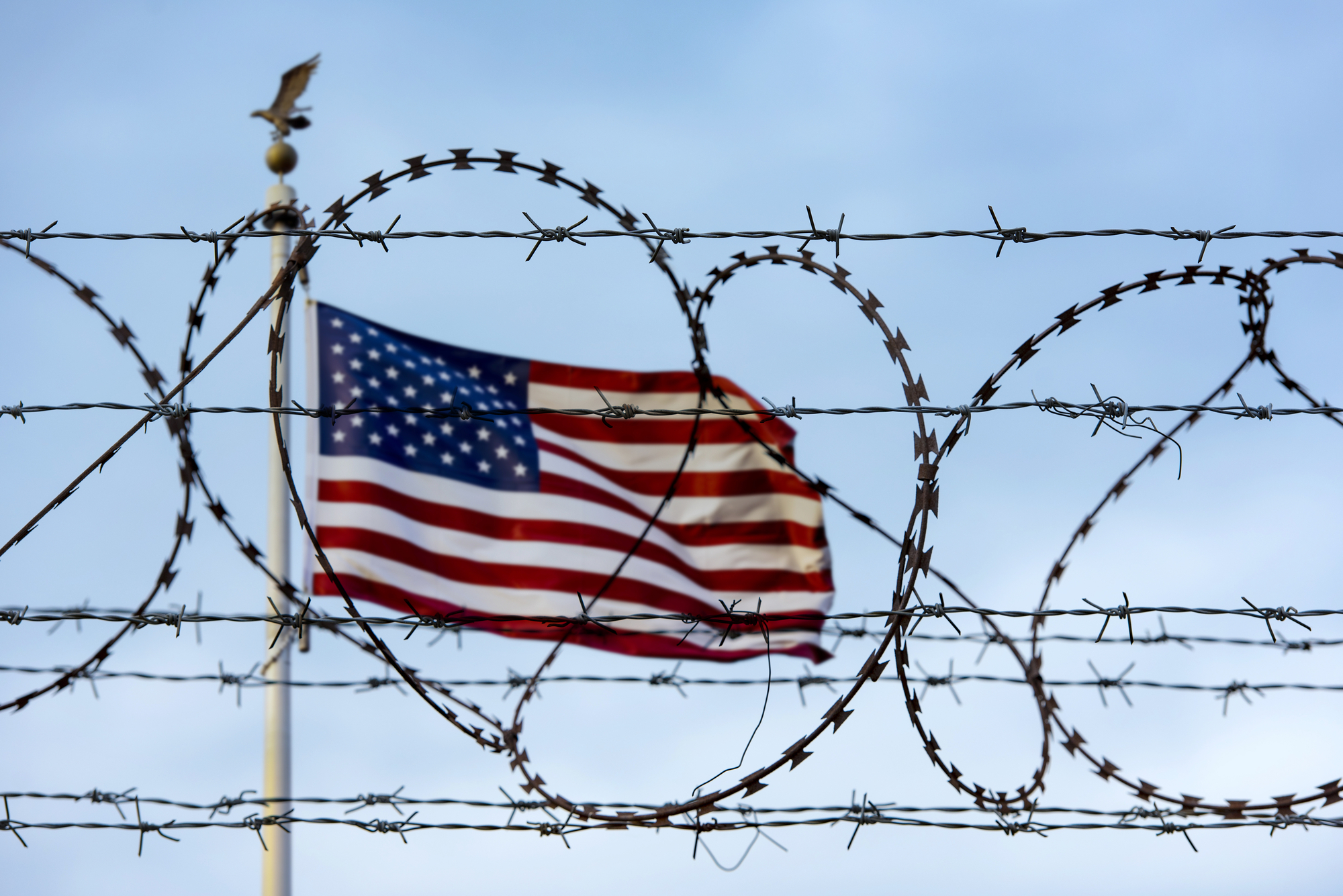 barbed wire in front of a U.S. flag