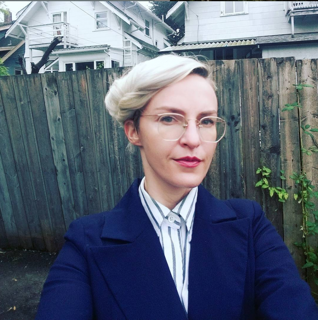 Dr. Ela Przybylo standing in front of wooden fence