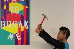 girl holding hammer next to painting