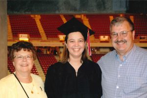 three people smiling, middle person wearing graduation apparel