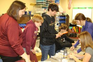 a teacher working on project with five students