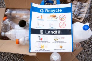 Reusable bag with graphic saying what can be recycled and what goes into the landfill. Recyclable: Plastic containers (bottles, tubs, jugs); Paper (flatten cardboard and mixed paper); Metal (steel and aluminum containers); Glass (unbroken bottles and jars); no food waste; no liquids; no plastic bags. Landfill: Beverage containers/utensils (beverage pods, drink/plastic solo cups, and straws); Food waste/containers (food, liquids, food containers, and Styrofoam); Plastic bags (snack bags, candy wraps, and packing materials); Paper napkins/towels/plates.