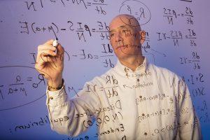 Professor writing on board.