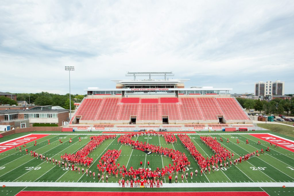 students on football field spelling out ISU