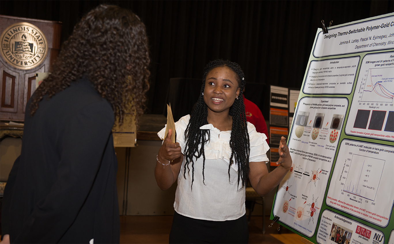 Woman talking to another person in front of a research poster