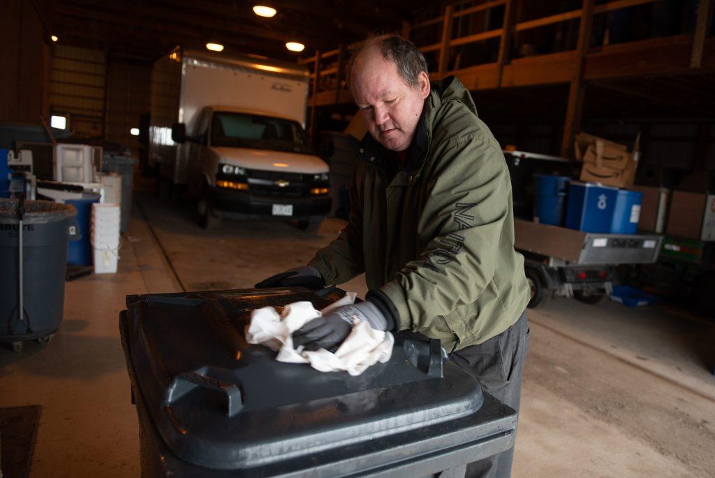 Man sanitizes recycling bin