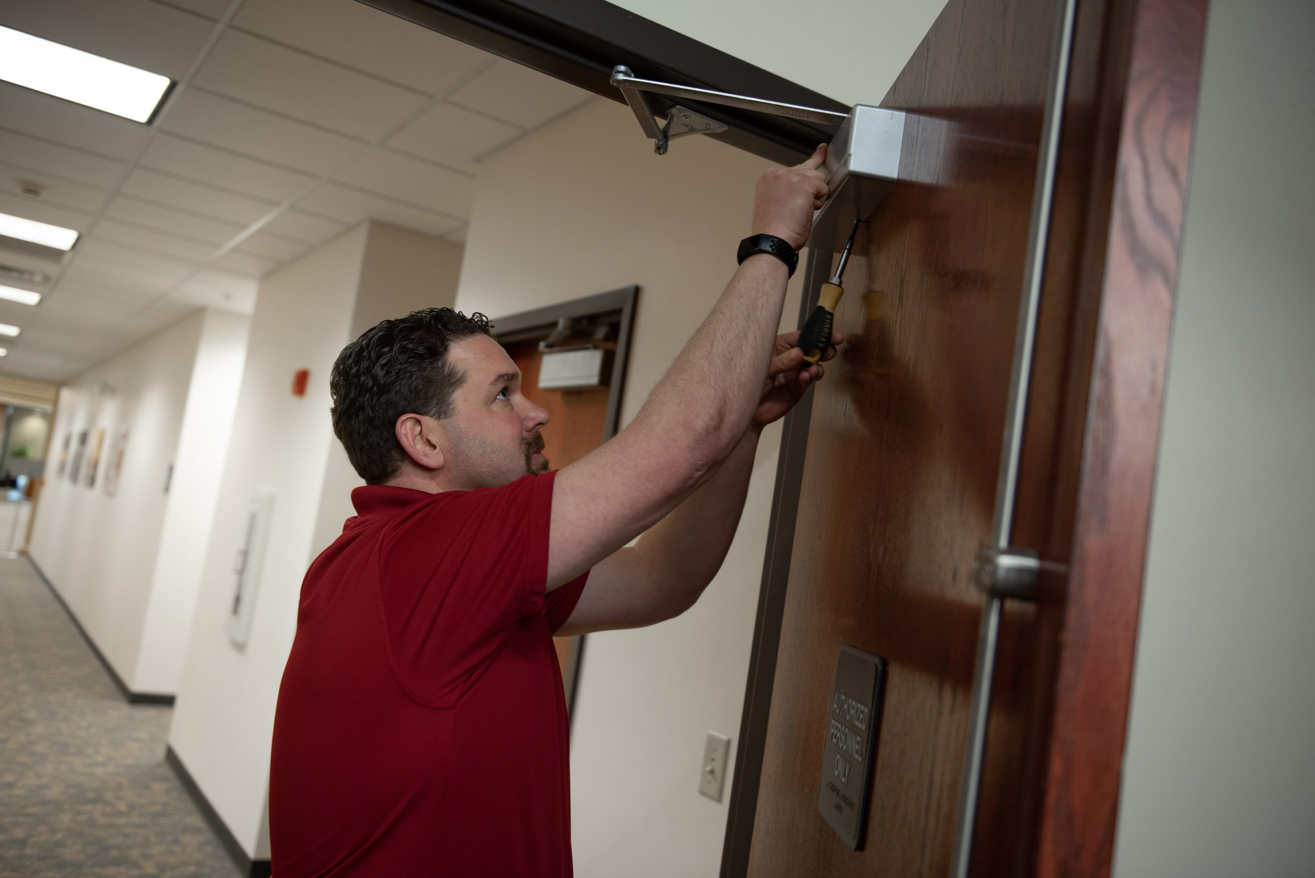 Carpenter Adam Moore checks to make sure that an exit door at the Alumni Center is closing properly.
