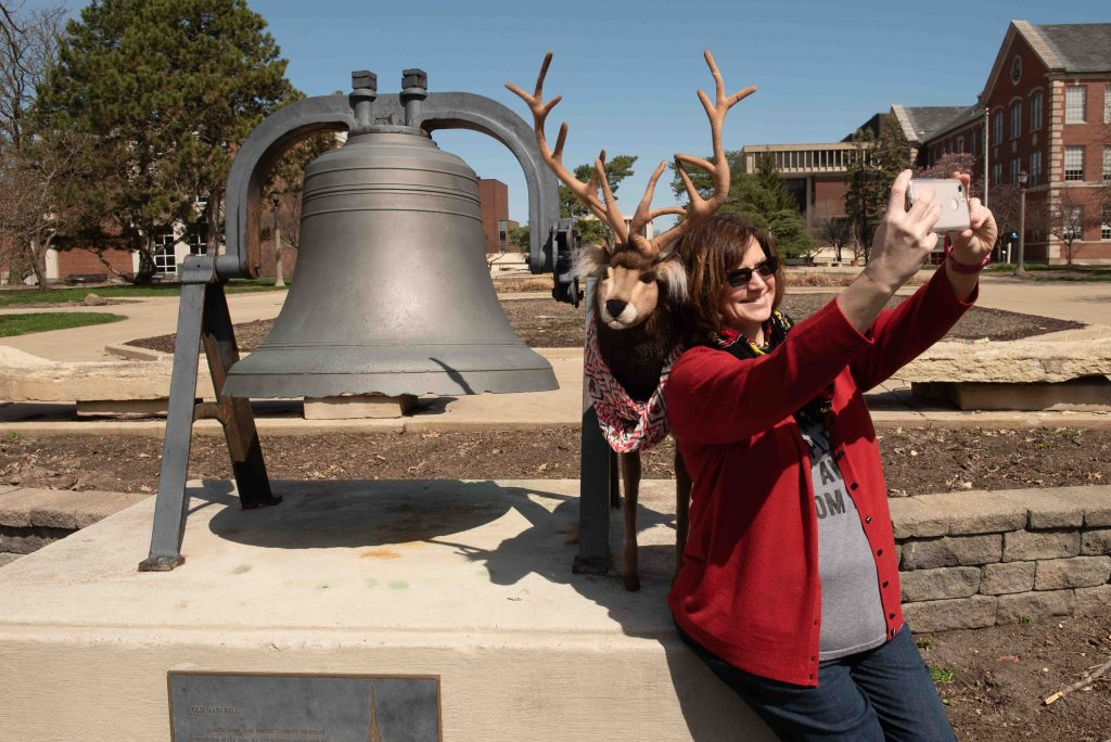 Woman takes selfie by bell