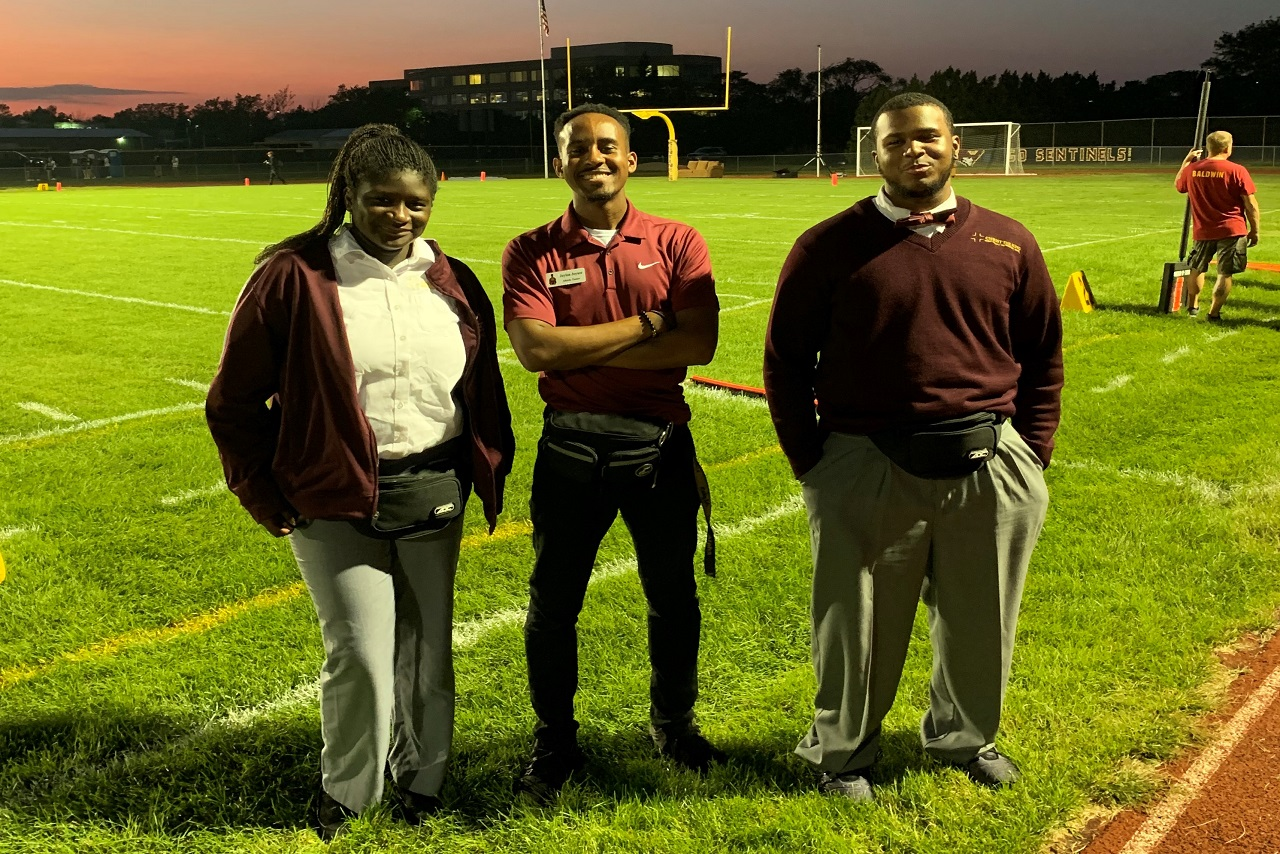 Three people standing on football field