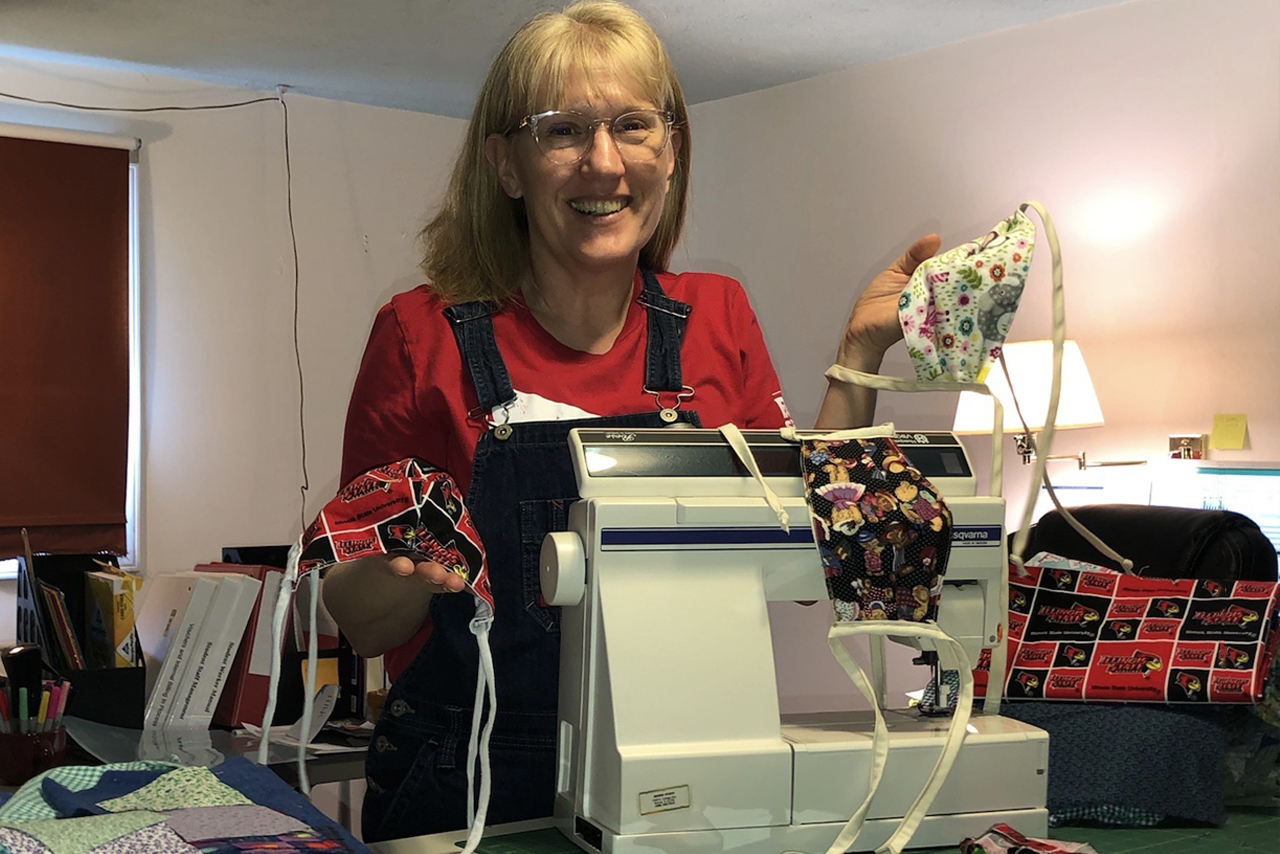 Beth Porter poses with masks and her sewing machine