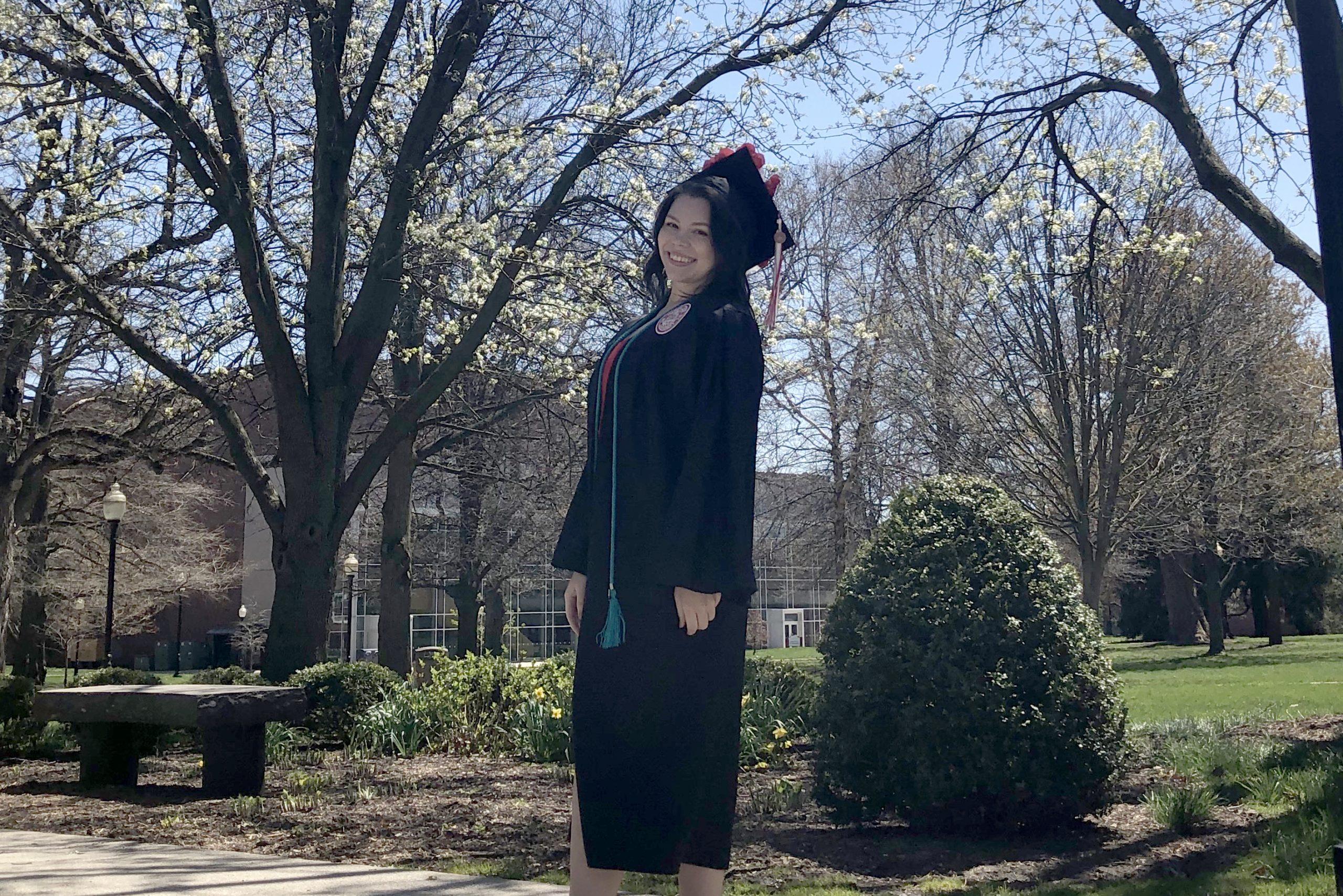 Student on Quad posing in graduation regalia