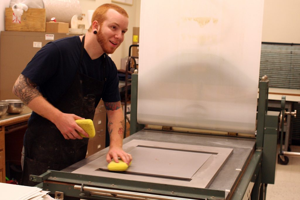 Student sponging a lithography plate