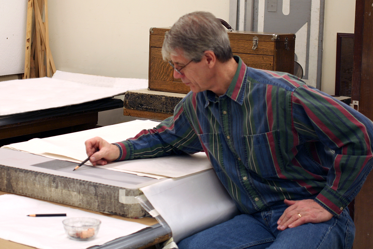 artist drawing on a lithography stone