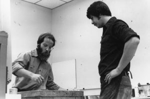 two artists working with a lithography stone on a press