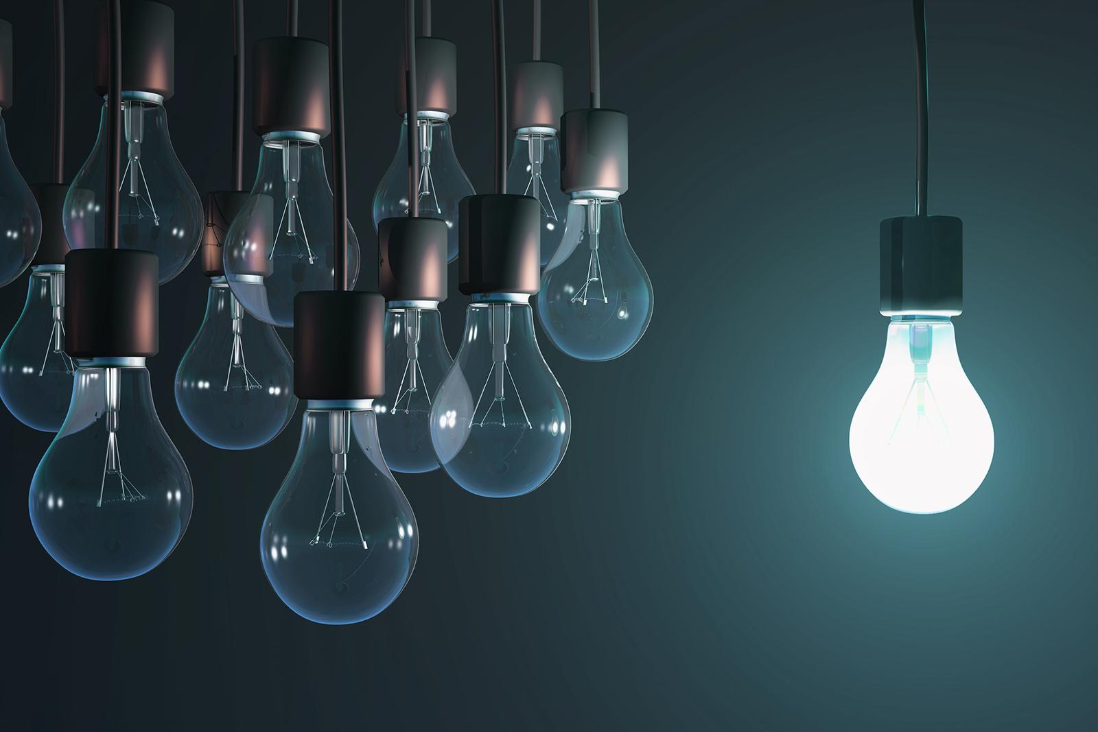 one lighted light bulb among the gray