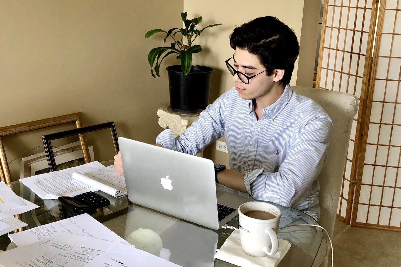 Man working at a laptop and a desk