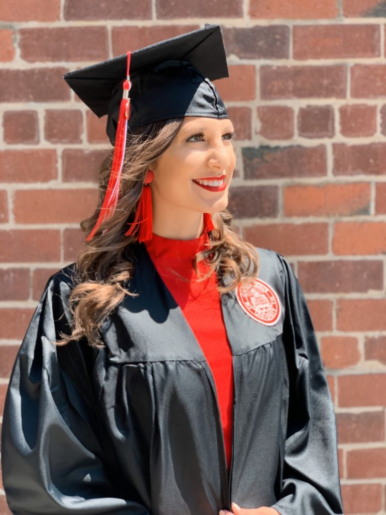Woman in cap and gown smiling