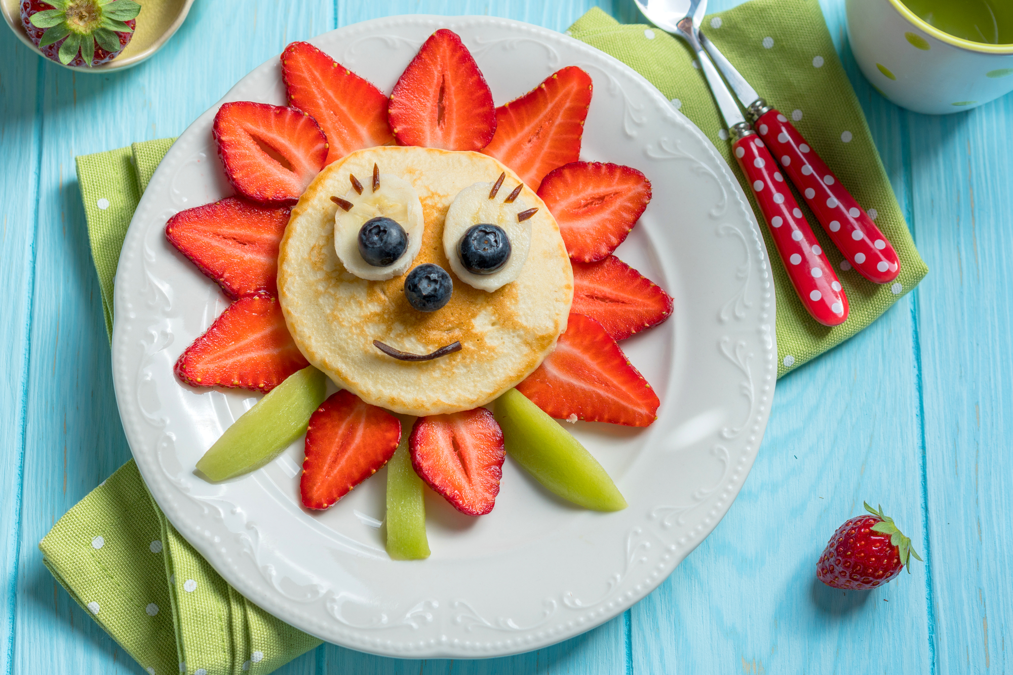 pancake shape dinto a sunflower with straberries for leaves and blueberries for a face