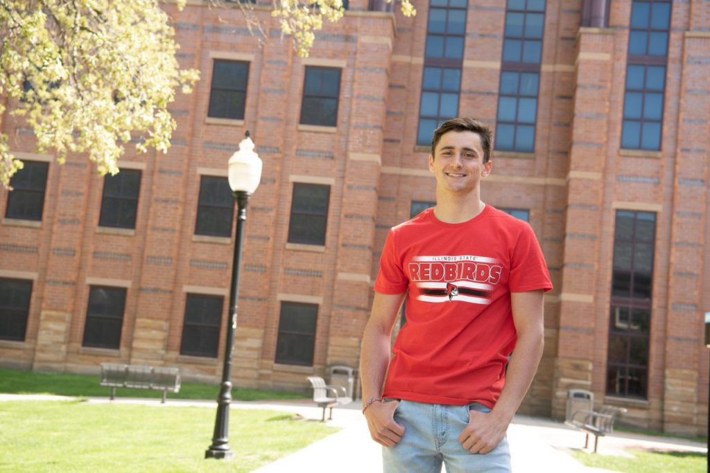 Young man standing in front of college building