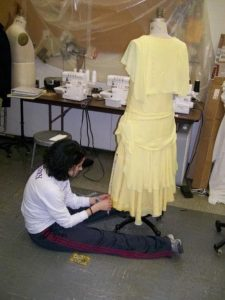 School of Theatre and Dance alumna Christina Leineke as a student working in the Costume Shop on a yellow dress for the production of MA RAINEY'S BLACK BOTTOM