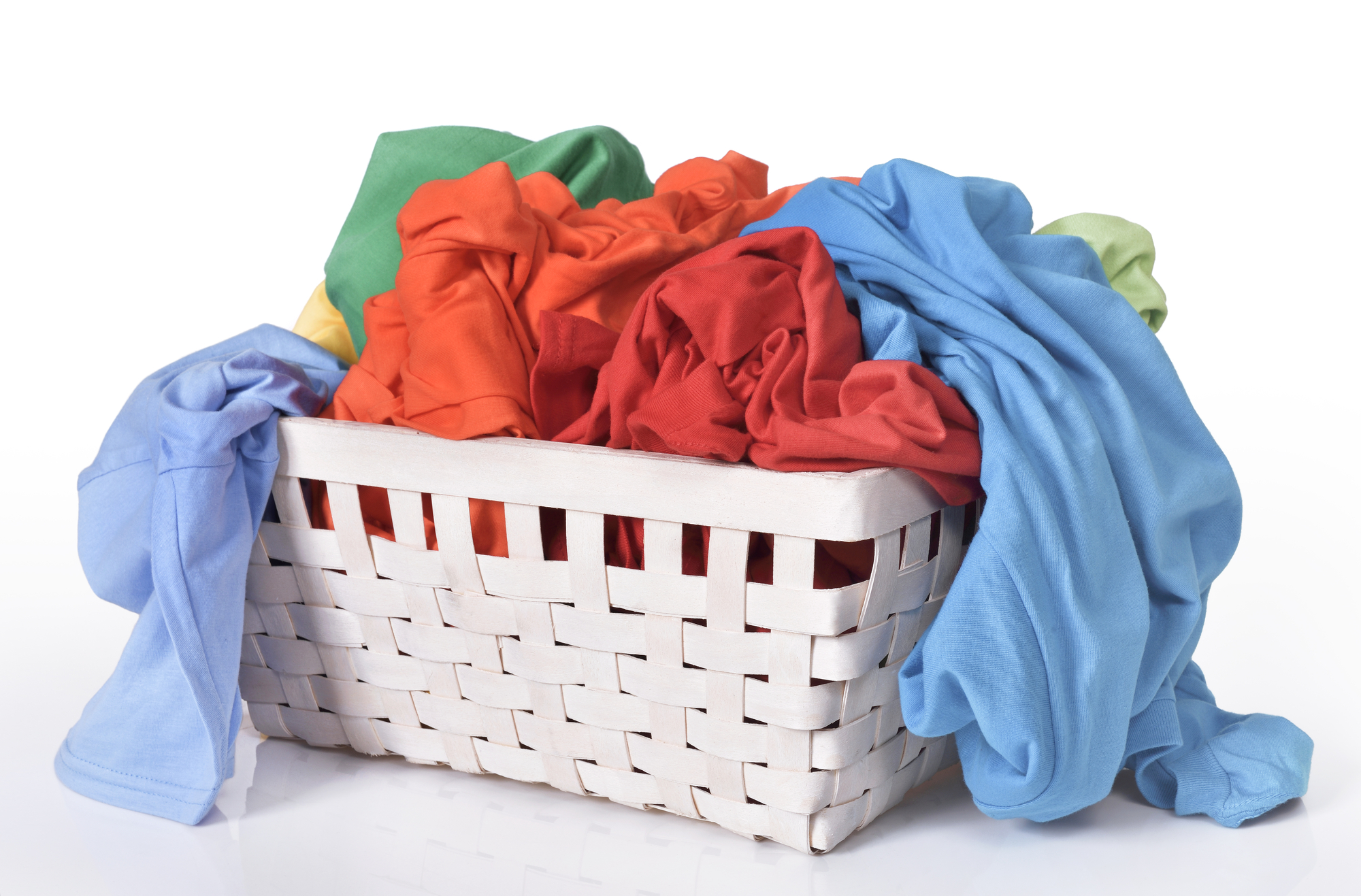 Colorful dirty clothes in laundry basket isolated over white background