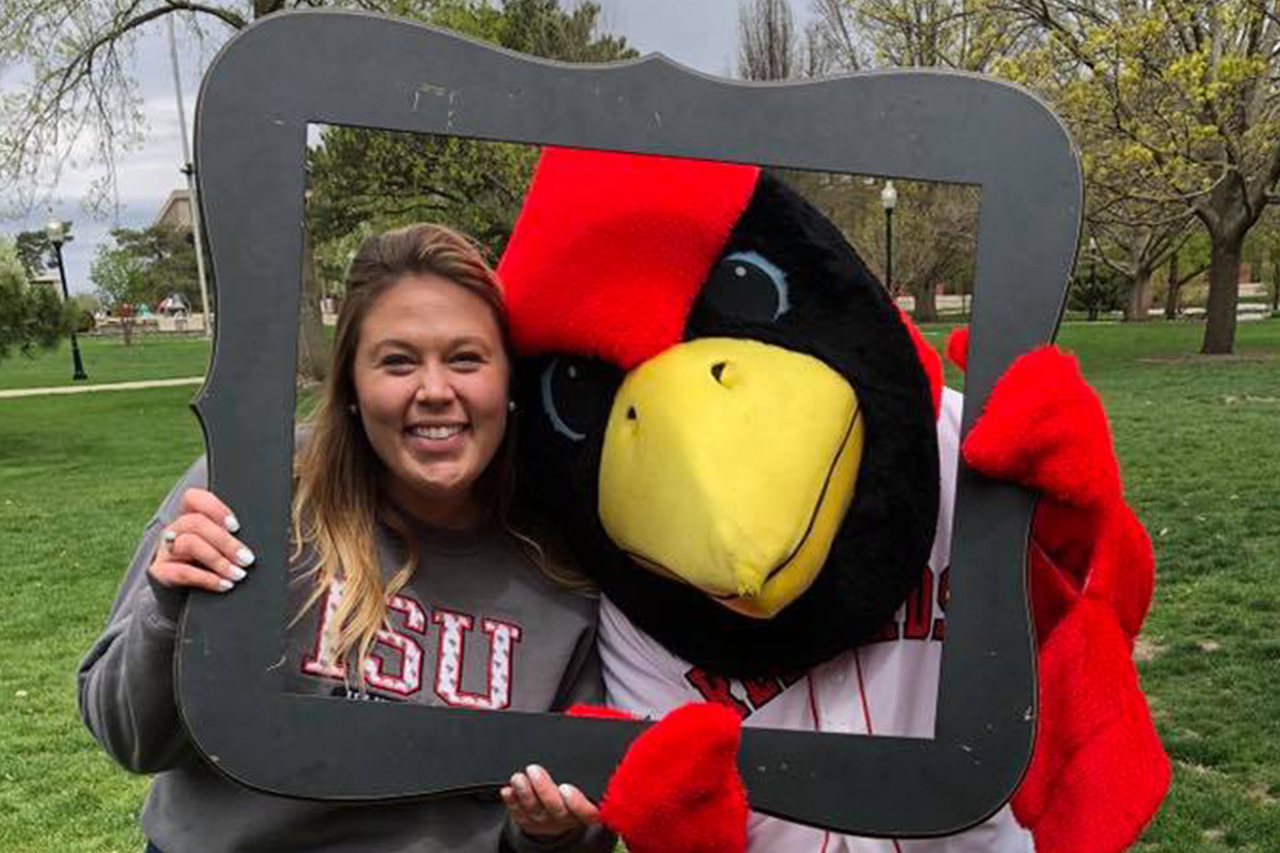 New staff member, Amanda Cox, smiles through a picture frame with mascot, Reggie Redbird
