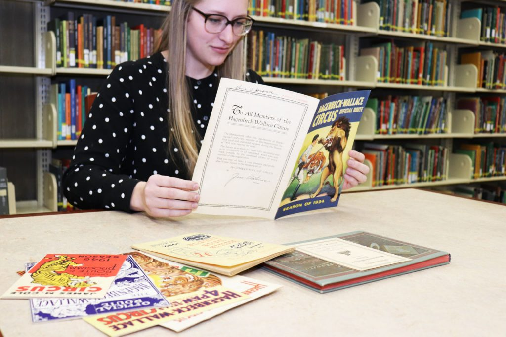 woman looking at circus route books