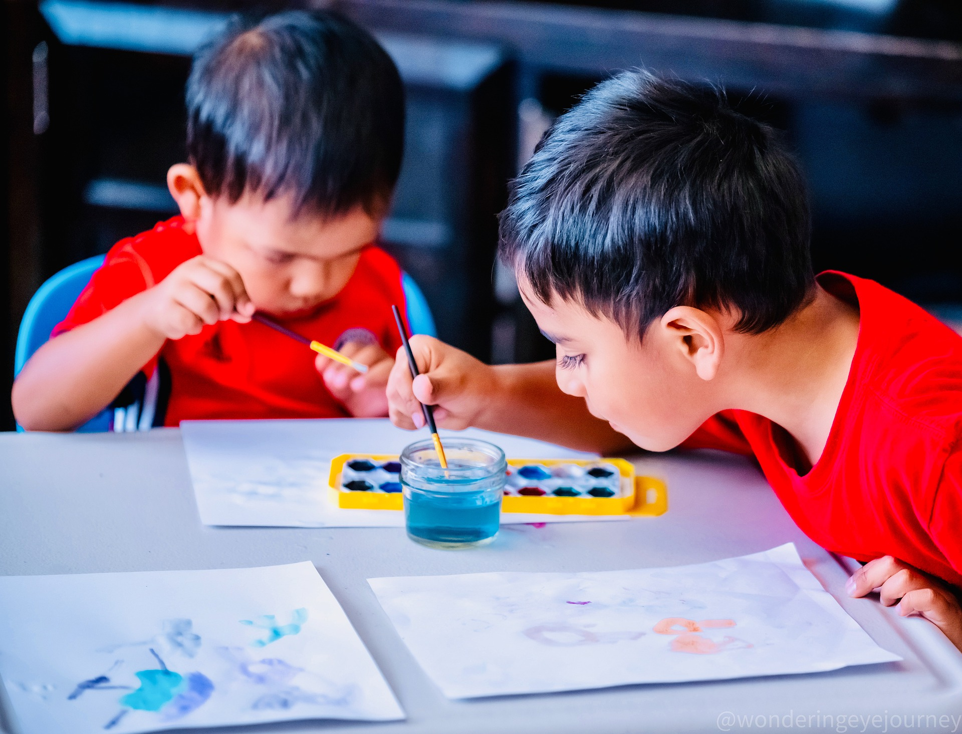 Two young students painting at a table